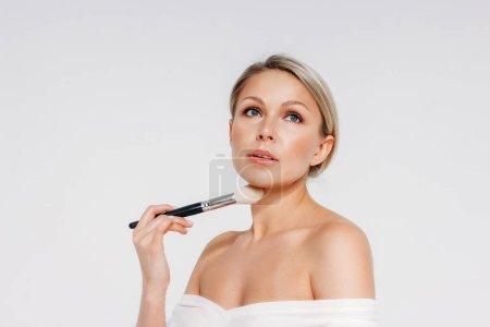 Photo pour Portrait de beauté de femme souriante blonde 35 ans plus tenant blush brosse près propre visage frais isolé sur le fond blanc - image libre de droit