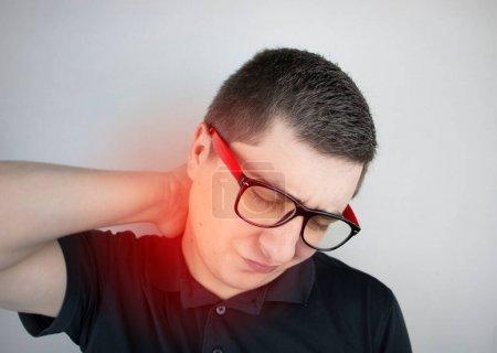 Un hombre sufre de dolor en el cuello, masajea la columna cervical con la mano. Osteocondrosis, hernia o lesión nerviosa debida a trabajo sedentario o estrés físico