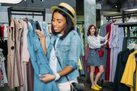 Photo pour Filles hipster multiculturelles choisir des vêtements dans le centre commercial, concept boutique shopping - image libre de droit