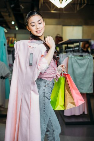 Photo for Asian hipster girl holding dress and shopping bags in boutique, clothes shopping concept - Royalty Free Image