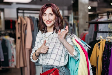Photo for Young hipster girl smiling with thumb up in boutique, clothes shopping concept - Royalty Free Image