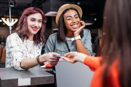 Photo pour Jeunes filles multiculturelles faisant du shopping et payant avec carte de crédit dans la boutique, concept de shopping de mode filles - image libre de droit