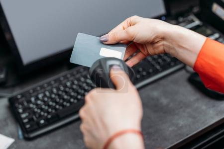 Photo for Close-up partial view of person using payment terminal and scanning credit card - Royalty Free Image