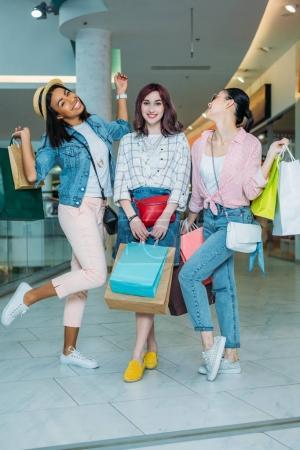 Photo pour Heureuses jeunes femmes élégantes avec des sacs à provisions posant dans le centre commercial, concept de shopping de jeunes filles - image libre de droit