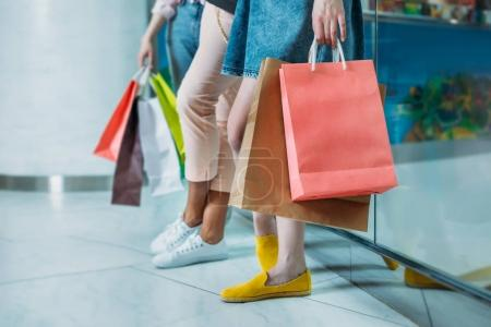 Photo for Cropped shot of young women with shopping bags standing in shopping mall, young girls shopping concept - Royalty Free Image