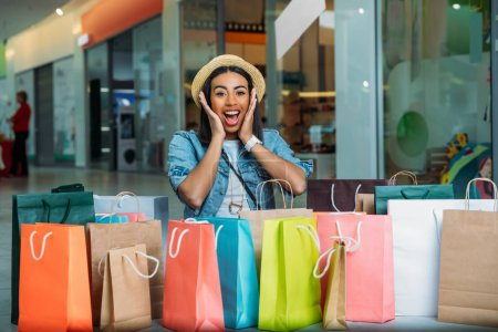 Photo for Shocked young woman looking at colorful shopping bags, boutique shopping concept - Royalty Free Image