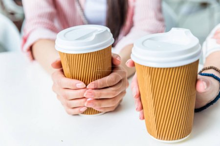 women holding cups of coffee