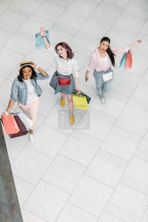 Photo pour Vue grand angle de jeunes femmes élégantes marchant avec des sacs à provisions, concept de shopping de jeunes filles - image libre de droit