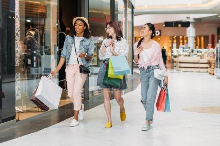 Photo pour Élégantes jeunes femmes souriantes marchant avec des sacs à provisions, concept de shopping de jeunes filles - image libre de droit