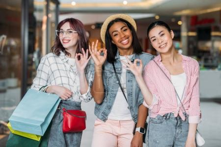 Photo for Portrait of smiling women with shopping bags showing ok signs at shopping mall - Royalty Free Image