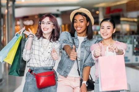 Photo pour Portrait de femmes souriantes avec des sacs à provisions montrant les pouces vers le haut des panneaux au centre commercial - image libre de droit