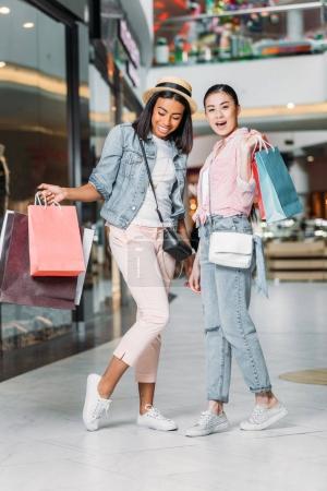 Photo pour Femmes élégantes amies faisant du shopping ensemble au centre commercial - image libre de droit