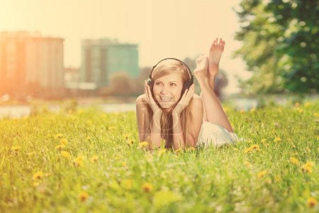 Photo for Beautiful smiling woman Woman listening to music on headphones outdoors - Royalty Free Image