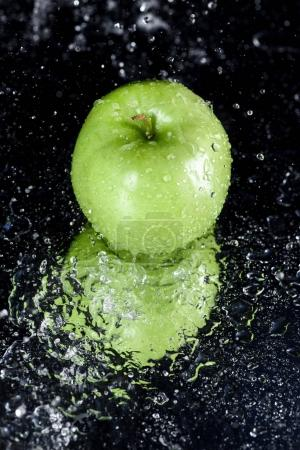 Photo for Green apple in water with reflection on black with copy space - Royalty Free Image