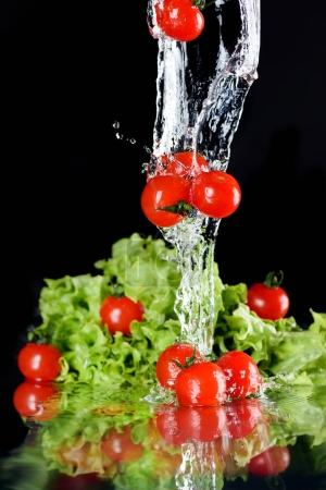 Photo for Red fresh cherry tomatoes and green lettuce in water  isolated on black, fresh vegetables falling in water splash concept - Royalty Free Image