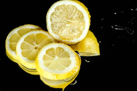 Photo for Close-up view of fresh sliced lemon with water drops isolated on black - Royalty Free Image