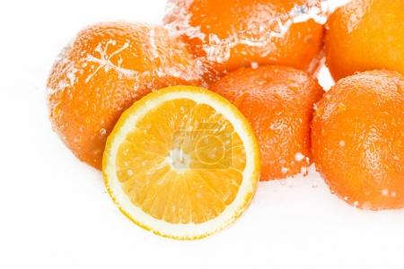 Photo pour Vue rapprochée d'oranges fraîches mûres avec gouttes d'eau isolées sur des fruits blancs et frais tombant dans l'eau - image libre de droit