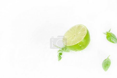Photo for Half of lime with green leaves and water drops isolated on white, fresh fruits background - Royalty Free Image