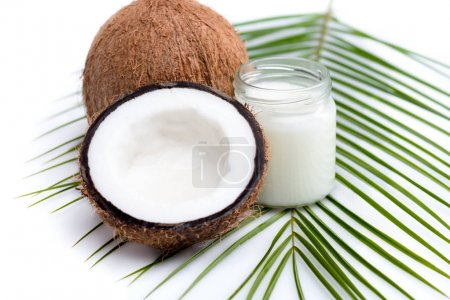 Photo for Ripe coconuts and organic coconut oil in glass jar on coconut leaf  isolated on white - Royalty Free Image