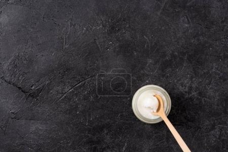 Photo pour Vue de dessus de l'huile de coco dans un bocal en verre avec cuillère sur fond noir - image libre de droit