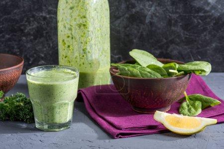 Photo pour Boisson antioxydante fraîche, bol de feuilles d'épinards et morceau de citron sur la table - image libre de droit