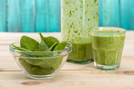 Photo for Green leaves in bowl and smoothie in glass and bottle on wooden table - Royalty Free Image