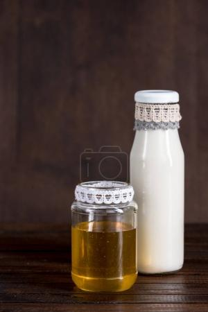 glass bottle of milk with honey in jar