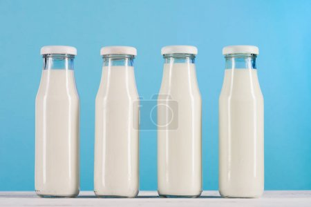 row of glass bottles with milk on tabletop