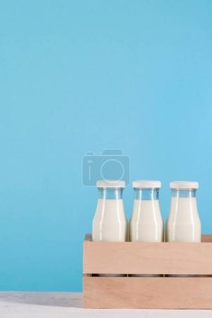 glass bottles with milk in wooden box
