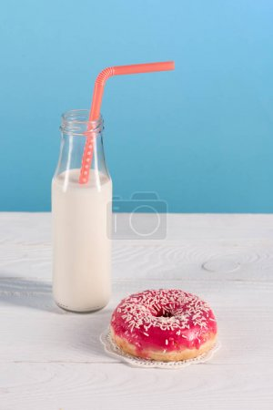 glass bottle of milk with donut on plate
