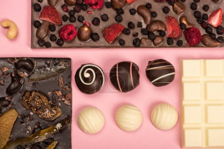 Photo for Flat lay with assorted chocolate bars with fruits and nuts and candies isolated on pink - Royalty Free Image