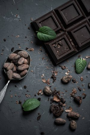 Photo pour Vue de dessus de la barre de chocolat et une cuillère avec des fèves de cacao et de feuilles de menthe - image libre de droit