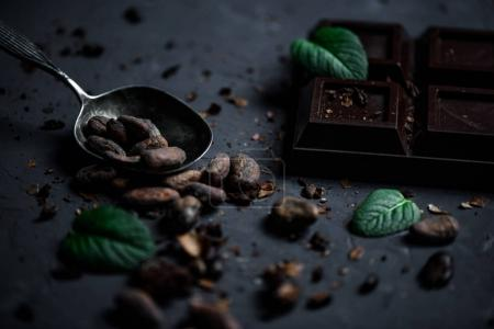 Photo pour Fermer la barre de chocolat et la cuillère avec des fèves de cacao et des feuilles de menthe - image libre de droit