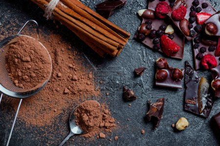 Photo for Pieces of chocolate bar with nuts and berries with cinnamon and sieve - Royalty Free Image