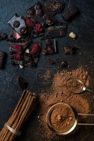 Photo pour Morceaux de barre de chocolat aux noix et baies avec cannelle et tamis - image libre de droit