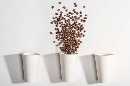 Photo pour Vue de dessus des gobelets en papier jetables blancs avec grains de café isolés sur blanc - image libre de droit