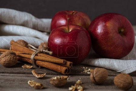 Photo for Three red apples, cinnamon sticks and walnuts on linen napkin on wooden tabletop - Royalty Free Image