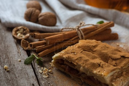 Photo for Homemade apple pie with cinnamon sticks and walnuts on rustic wooden tabletop - Royalty Free Image