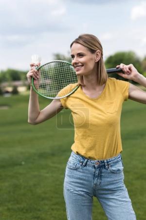 Photo pour Jolie femme souriante debout avec la raquette de badminton et volant dans le parc - image libre de droit