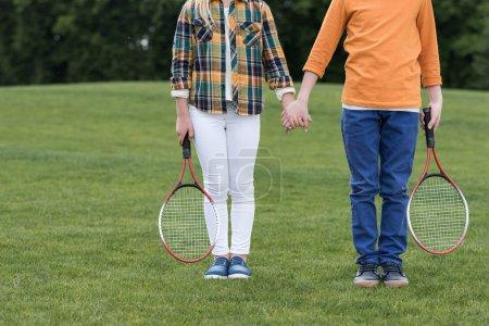 Photo pour Recadrée tir de frères et sœurs avec raquettes de badminton, main dans la main, debout sur l'herbe verte - image libre de droit