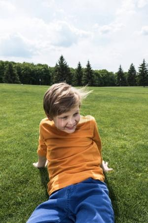 boy resting on green lawn