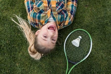 Photo pour Vue de dessus de fille excitée regardant la caméra avec l'équipement de badminton à proximité - image libre de droit