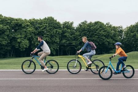 Photo pour Vue latérale des parents souriants et du petit fils faisant du vélo ensemble dans le parc - image libre de droit