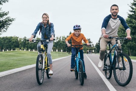 Photo for Smiling parents and little son riding bicycles together in park - Royalty Free Image