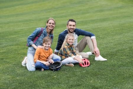 Photo for Smiling family looking at camera while sitting on the grass at park - Royalty Free Image
