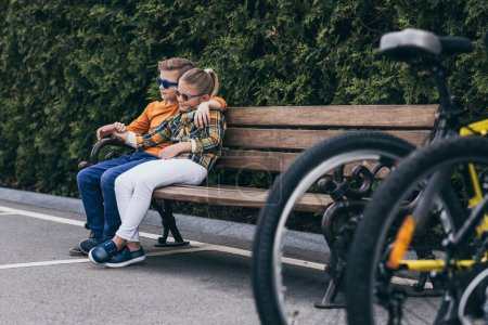 Photo for Stylish kids in sunglasses embracing while resting on bench at park - Royalty Free Image