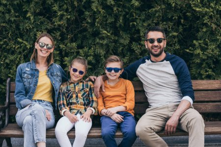 smiling family in sunglasses sitting on bench