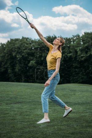 young woman playing badminton at park