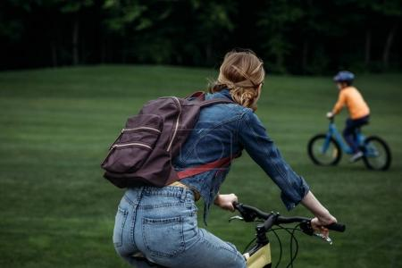 woman with backpack riding bicycle at park