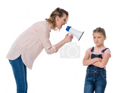 Photo for Angry mother with megaphone screaming at little daughter standing with crossed arms - Royalty Free Image
